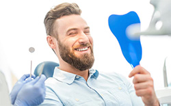 Man smiling in mirror at dentist
