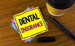 Dental insurance written on yellow notepad