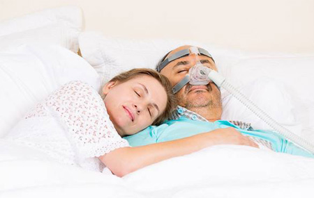 Woman sleeping in bed with man wearing a CPAP mask