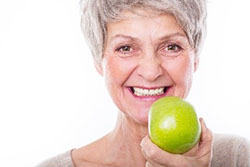 Elderly woman holding apple